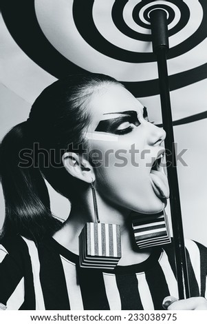 portrait of woman licking stick of spiral umbrella in studio - stock photo
