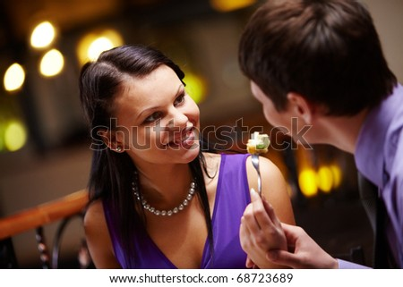 Portrait of woman looking at man and holding fork with food