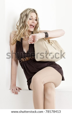 portrait of woman looking at wristwatch - stock photo