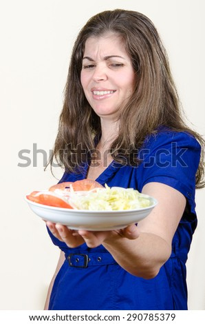 Portrait of woman looking with disgust at the plate of food - stock photo