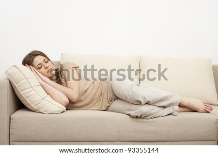 Portrait of woman lying on sofa and slipping. Casual style indoor shoot. - stock photo