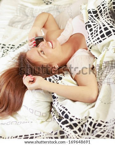 Portrait of woman making a phone call while lying on her bed - stock photo