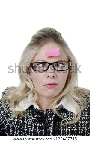 Portrait of woman making funny face while having sticky note on her forehead - stock photo