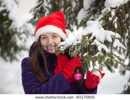 Portrait of  woman near fir-tree in winter