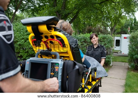 Portrait of woman on emergency medical team taking patient to hospital - stock photo