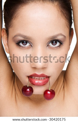 portrait of woman on white holding red cherries on her lips - stock photo