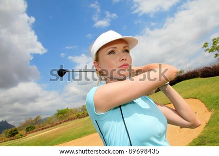 Portrait of woman playing golf - stock photo