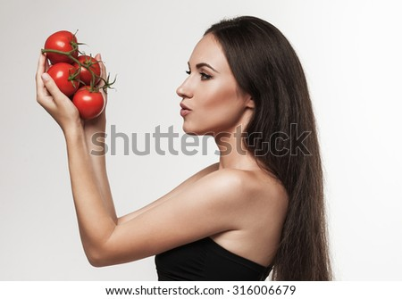 Portrait of woman promoting healthy eating. Beautiful young brunette woman with slim body holding fresh glossy red tomatoes. Healthy eating lifestyle and weight loss concept.  Studio white background. - stock photo