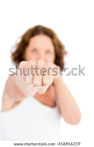 Portrait of woman punching while standing against white background