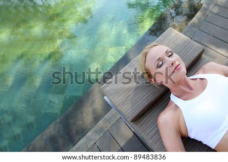Portrait of woman relaxing in deck chair - stock photo