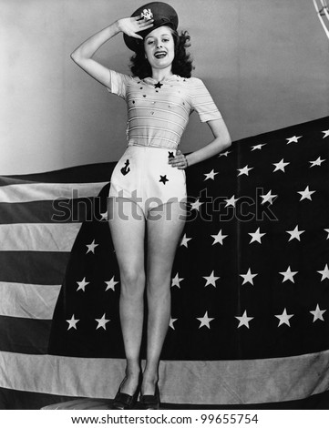 Portrait of woman saluting with American flag