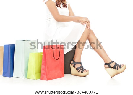 portrait of woman sitting next to shopping bags isolated on white background
