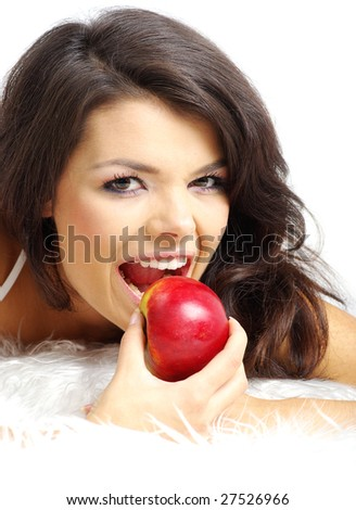 Portrait of  woman sitting on bed and eating fresh red apple