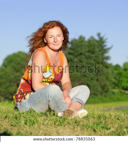 Portrait of woman sitting on grass in park - stock photo