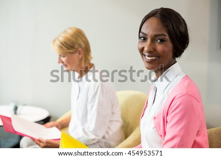 Portrait of woman smiling at camera while her colleague reading document in the office