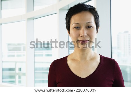 Portrait of woman standing by windows - stock photo