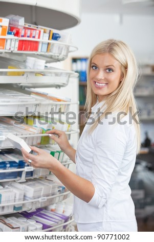 Portrait of woman standing in pharmacy drugstore holding medication box - stock photo