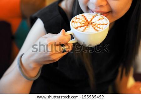 Portrait of woman tasting capuchino coffee  - stock photo