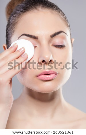 Portrait of woman using cotton pad over grey background