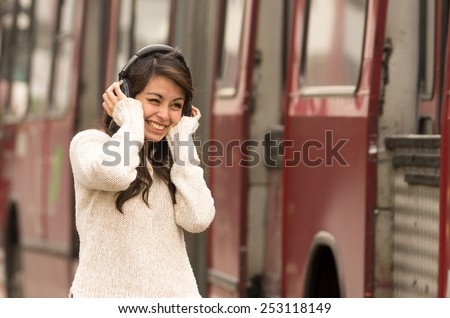 portrait of woman walking on the city street wearing headphones concept of noise pollution - stock photo