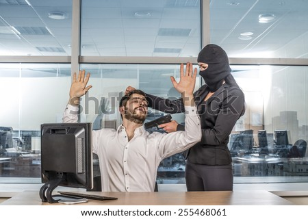 Portrait of woman wear black balaclava hold hair with gun look at hostage scared business man on reflection window background Empty space for inscription Girl sit on table near pc computer Hands up - stock photo