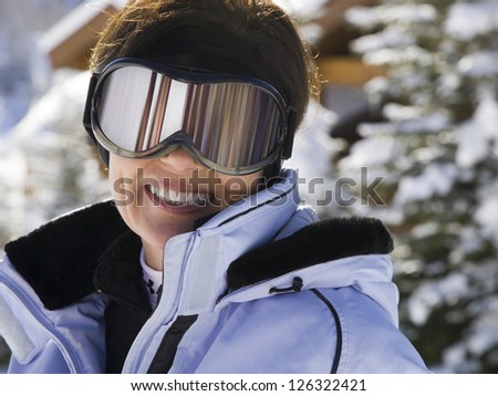 Portrait of woman wearing ski goggles outdoors