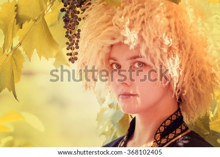 Portrait of woman wearing traditional felt cloak and fur cap outdoor in the grape garden