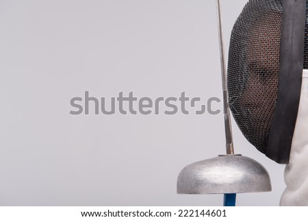 Portrait of woman wearing white fencing costume standing aside holding the sword in front of her. Isolated on white background - stock photo