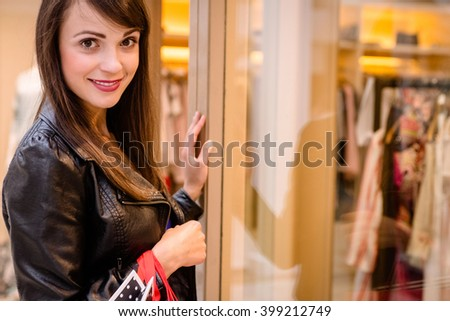 Portrait of woman window shopping outside a shop in shopping mall - stock photo