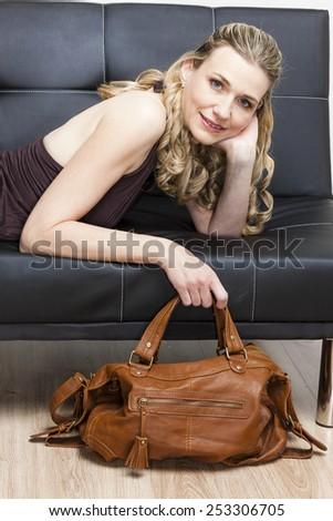 portrait of woman with a handbag lying on sofa - stock photo