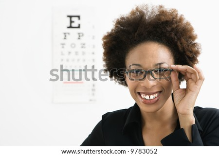 Portrait of woman with afro wearing eyeglasses with medical eyechart in background. - stock photo