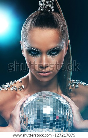 Portrait of woman with artistic make-up and rhinestones over background - stock photo