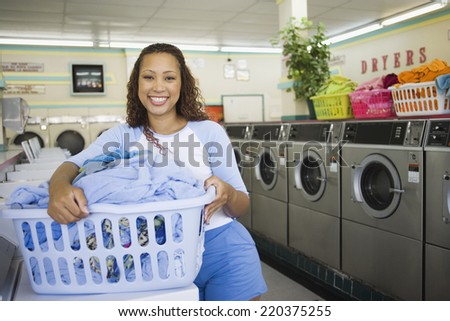 Portrait of woman with basket of clothes in laundromat - stock photo