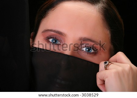 portrait of woman with beautiful blue eyes, covers her face