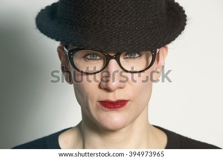 portrait of woman with black hat and glasses looking serious