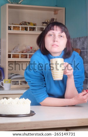 Portrait of woman with cup against kitchen interior background.