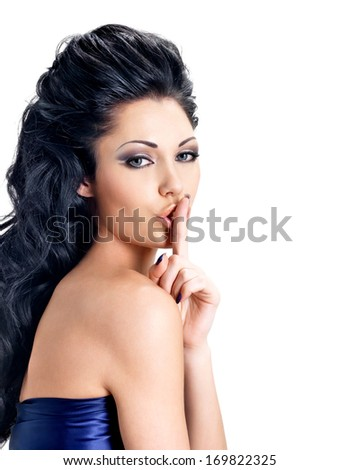 Portrait of woman with  expression silent.  Photo of brunette girl with finger near lips, concept of silence