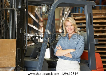 Portrait Of Woman With Fork Lift Truck In Warehouse