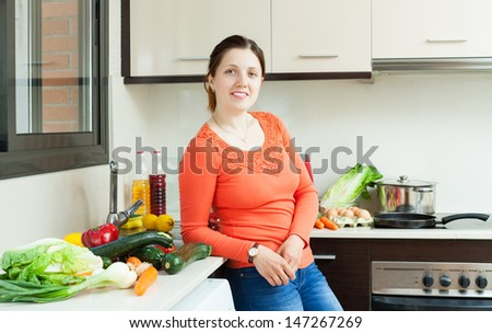 Portrait of woman with fresh vegetables in home kitchen