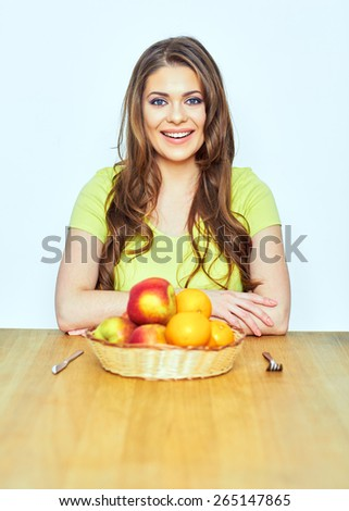 Portrait of woman with fruit. Smiling model sitting at the  table.
