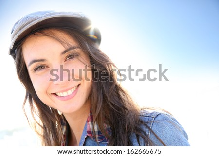 Portrait of woman with hat on a sunny day - stock photo