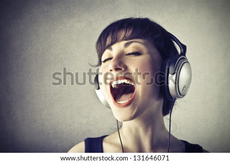 portrait of woman with headphones music singing - stock photo