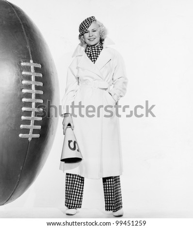Portrait of woman with huge football - stock photo