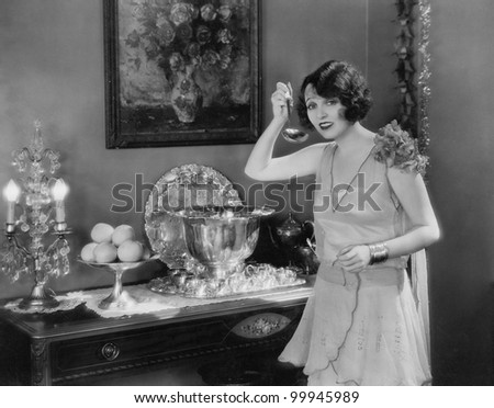 Portrait of woman with ladle and punch bowl - stock photo