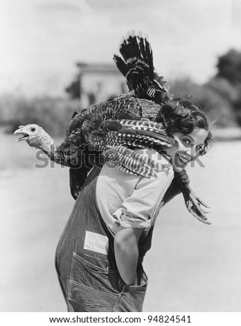 Portrait of woman with live turkey slung over shoulder - stock photo