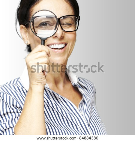 portrait of woman with looking through a magnifying glass against a grey background - stock photo