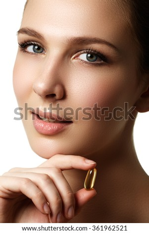 Portrait of woman with Omega 3 fish oil capsule, outdoors. Food Supplement. Portrait of young woman with Omega 3 fish oil capsule, isolated over white background - stock photo