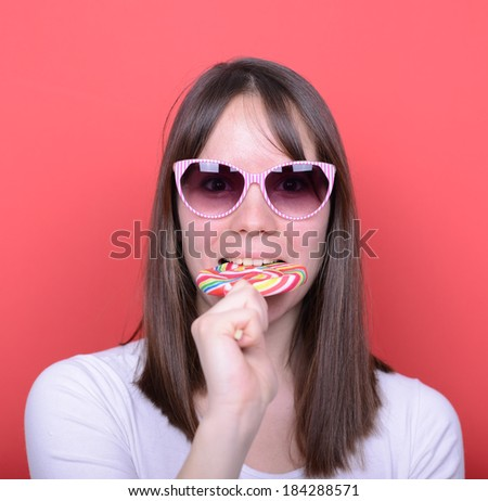 Portrait of woman with retro glasses and lollipop against red background