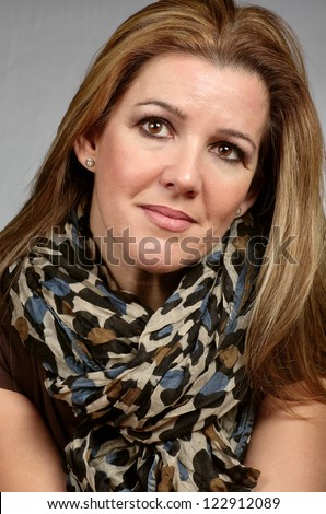 portrait of woman with scarf on gray background - stock photo