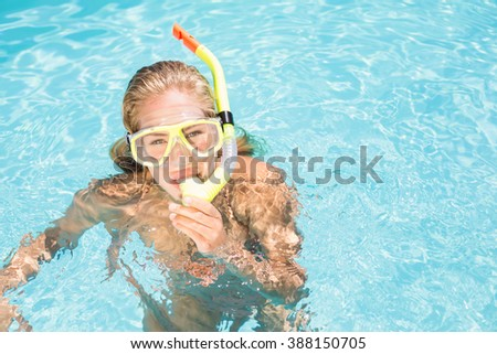 Portrait of woman with snorkel gear swimming in pool on a sunny day - stock photo